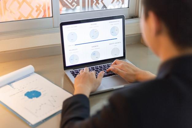 Zakelijke partners concept een jonge zakenman met behulp van een laptop herziening van de jaarlijkse verkoop samenvatting.