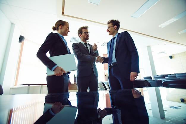 Zakelijke partners de handen in de vergaderzaal schudden