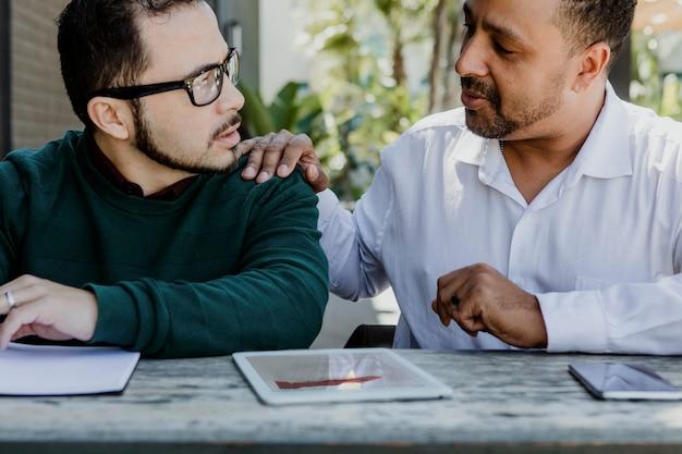 Zakelijke partners die digitale apparaten gebruiken in een café
