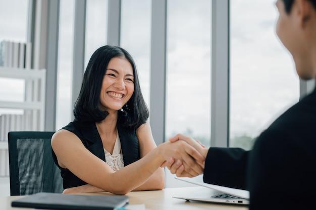 Zakelijke partners die elkaar de hand schudden om een klein bedrijf op te starten in de kantoorruimte.