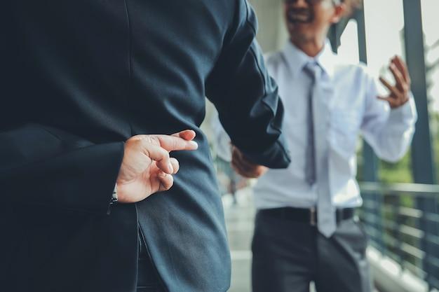 Zakelijke partners handen schudden met een van hen met vingers gekruist achter rug.