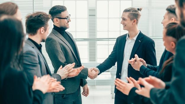 Zakelijke partners handen schudden voor het applaus van het zakelijke team. concept van succes