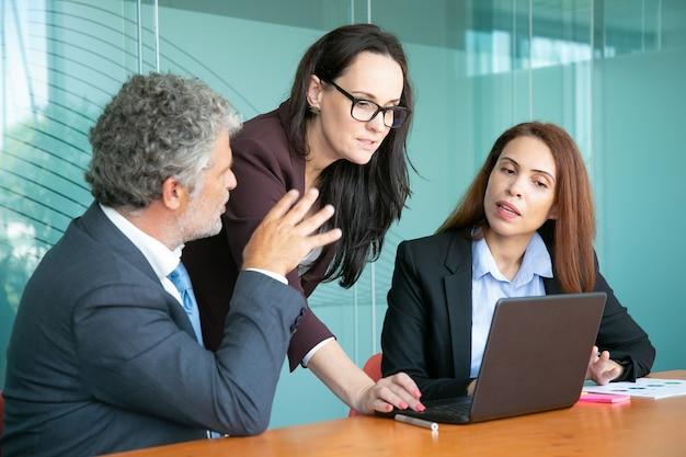 Zakelijke partners kijken naar presentatie en project bespreken tijdens vergadering.