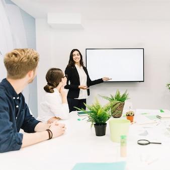 Zakelijke partners kijken naar vrouwelijke manager die presentatie geeft
