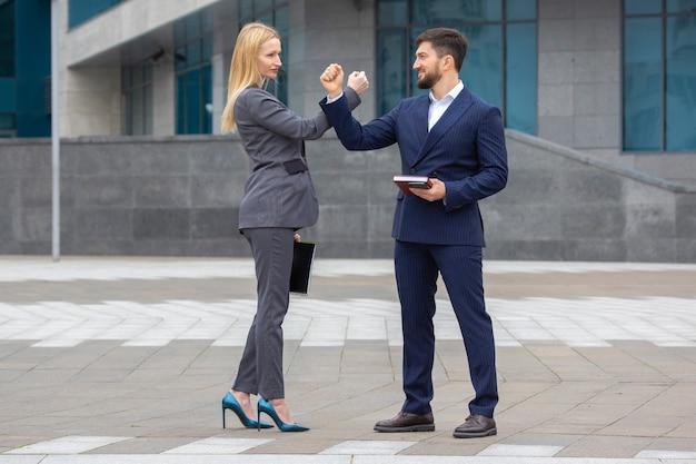 Zakelijke partners man en vrouw begroeten elkaar met hun handen