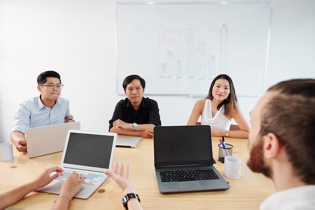 Zakelijke partners met leider tijdens bijeenkomst