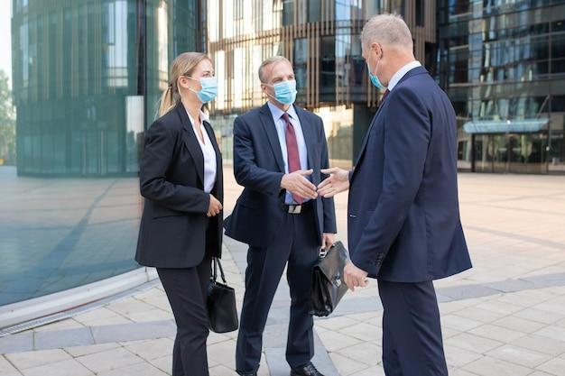 Zakelijke partners met professionele inhoud in gezichtsmaskers ontmoeten elkaar buitenshuis en begroeten elkaar. zelfverzekerde zakenmensen die werken tijdens de coronaviruspandemie. teamwork en partnerschap concept