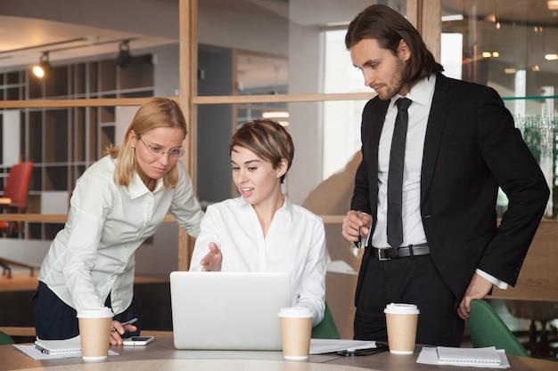 Zakelijke partners onderhandelen over strategieën met behulp van laptop