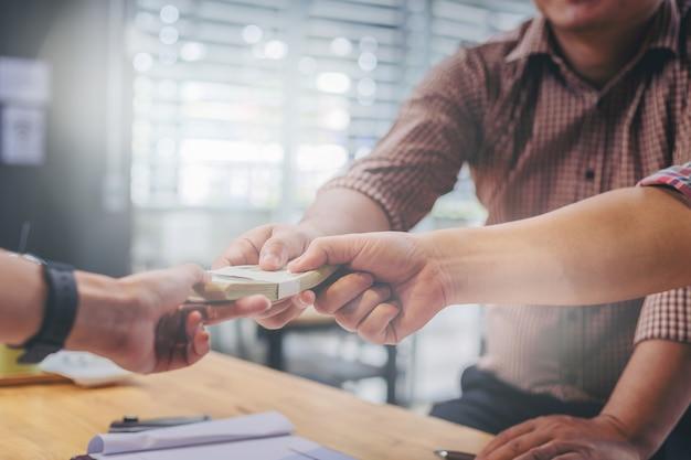 Zakelijke partners ontmoeten en geld doorgeven voor nieuw zakelijk project op tafel.