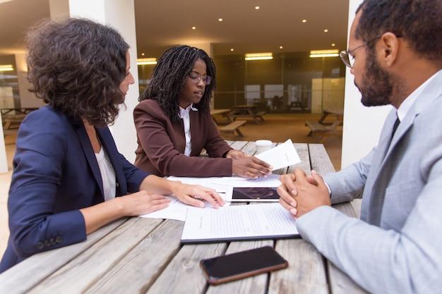 Zakelijke partners raadplegen juridische expert in openluchtcafé
