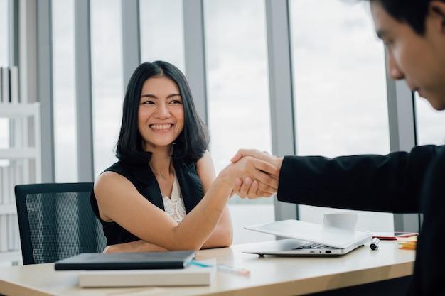 Zakelijke partners schudden elkaar de hand om een klein bedrijf op te starten in de kantoorruimte.
