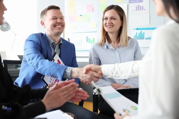 Zakelijke partners schudden elkaar de hand tijdens vergaderingen met collega's