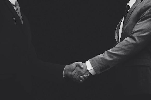 Zakelijke partners schudden handen monochroom