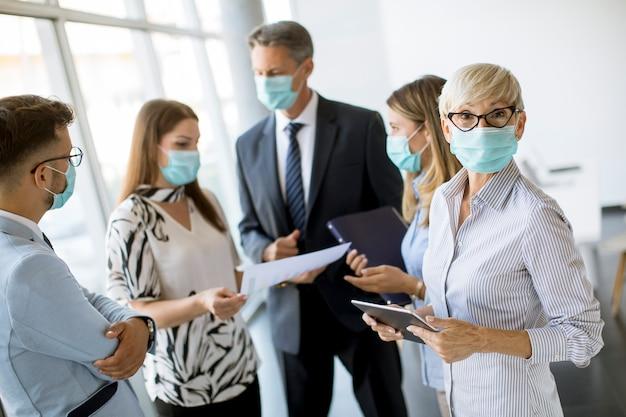 Zakelijke partners staan en kijken naar bedrijfsresultaten op kantoor terwijl ze gezichtsmaskers dragen, is een virusbescherming