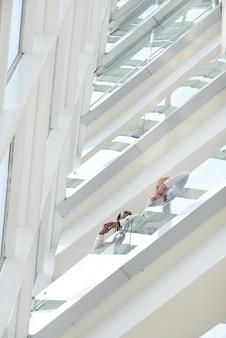 Zakelijke partners staan op het balkon van een modern kantoorgebouw en bespreken belangrijke kwesties