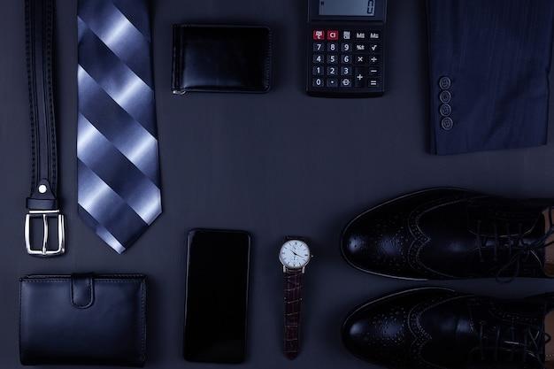 Zakelijke plat lag achtergrond met een kopie ruimte. mannelijke schoenen, polshorloge portemonnee, riem, mobiele telefoon en een stropdas op zwarte achtergrond.
