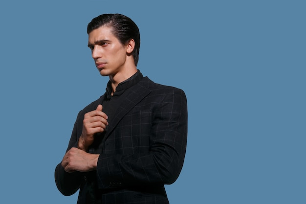 Zakelijke portret van een knappe fit jonge man in zwart pak schikken haar mouw, op blauwe achtergrond. horizontale weergave.
