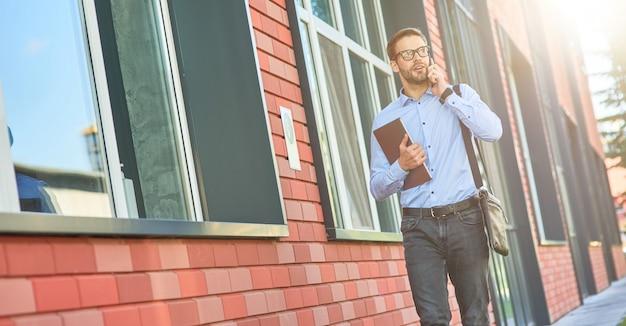 Zakelijke praat jonge zelfverzekerde blanke zakenman met een blauw shirt en een bril met zijn
