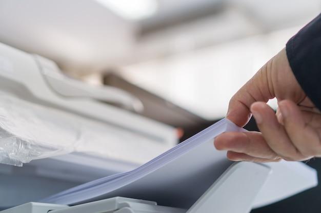 Zakelijke printer afdrukken van documenten in kantoorconcept zakenman drukt wit papier in laser afgedrukt
