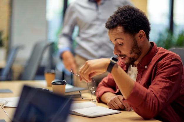 Zakelijke problemen jonge gefrustreerde en verdrietige man van gemengd ras die aan een bureau zit en werkt