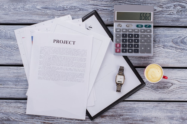 Zakelijke projectpapieren met rekenmachine en kopje koffie. bovenaanzicht plat lag. witte houten tafel op de achtergrond.