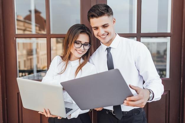 Zakelijke stijl. jonge mooie vrouw met een bril en een man in een zakelijke afbeelding met een laptop in hun handen glimlachend