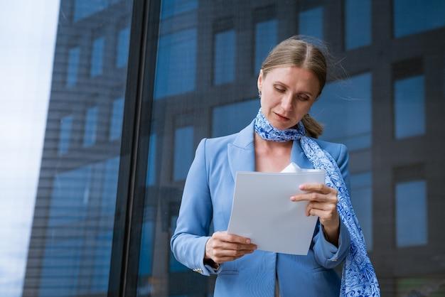 Zakelijke succesvolle blanke vrouw in blauwe jas houdt documenten in de hand in de buurt van kantoorgebouw