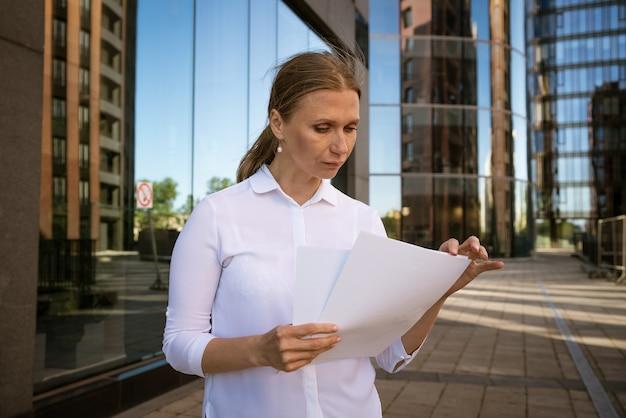 Zakelijke succesvolle vrouw met papieren in de hand tegen de achtergrond van het kantoorcentrum