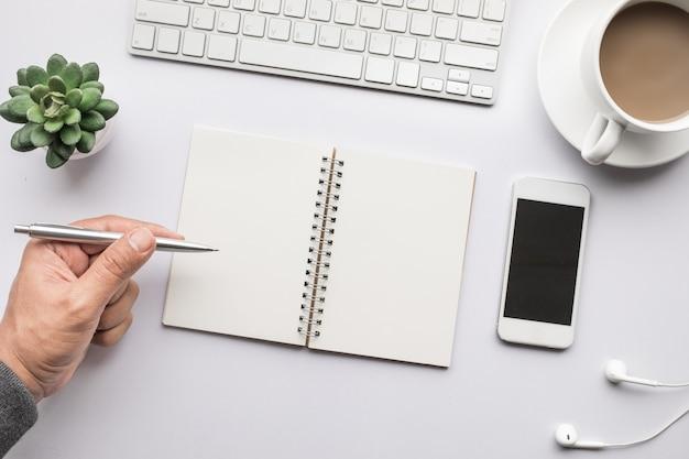 Zakelijke tafelblad met kantoorbenodigdheden en mannenhand op wit