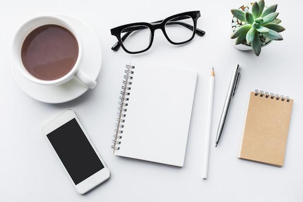Zakelijke tafelblad met kantoorbenodigdheden op witte achtergrond.