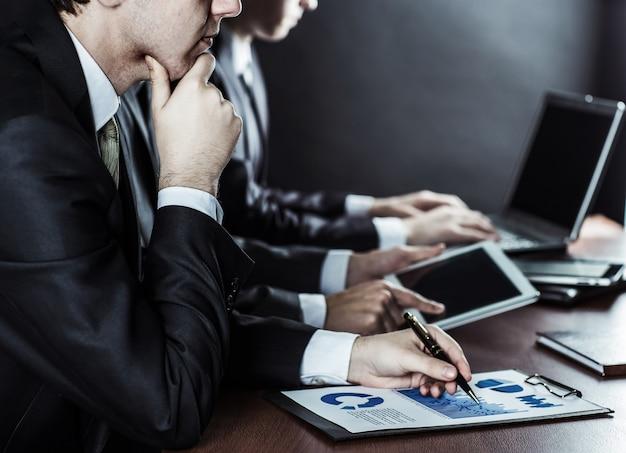 Zakelijke team met digitale tablet en financiële grafieken voor de werkplek op kantoor