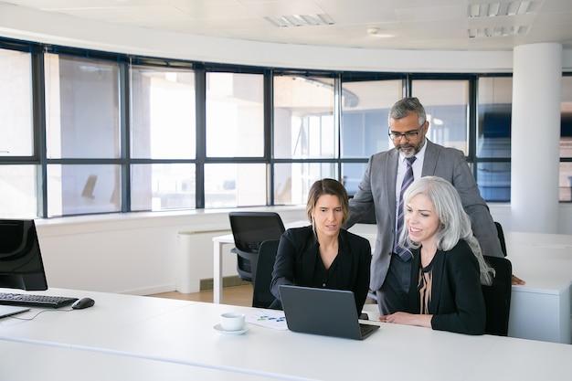 Zakelijke team van drie kijken naar presentatie op pc-monitor, project bespreken, zittend op de werkplek en wijzen op display. kopieer ruimte. zakelijke bijeenkomst concept