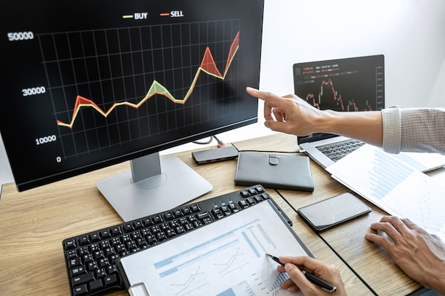 Zakelijke teaminvesteringen werken met computer, plannen en analyseren van grafiekbeurshandel