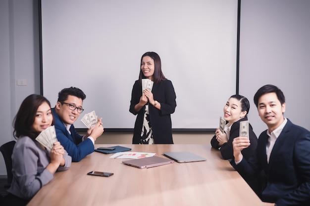 Zakelijke teamprestaties en ontvang de dollarsbankbiljetten van de baas tijdens de vergadering