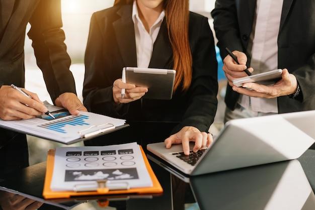 Zakelijke teamvergadering. professionele investeerder werkt nieuw startproject. financieringstaak. met slimme telefoon en laptop en digitale tabletcomputer in ochtendlicht