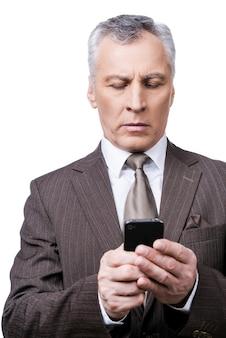 Zakelijke technologieën. zelfverzekerde volwassen man in formalwear die mobiele telefoon vasthoudt en ernaar kijkt terwijl hij tegen een witte achtergrond staat