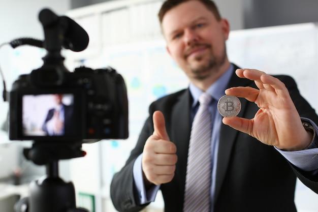 Zakelijke trainer houdt zilveren bitcoin in de hand