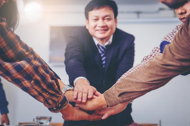 Zakelijke volkeren sluiten zich aan bij hun handen. teamwerk krachtig delen tijdens een vergadering.