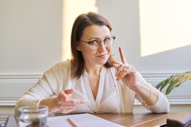 Zakelijke volwassen vrouw kijken naar webcam die videoconferentie geeft. vrouwelijke verkoper in gesprek met klant, leraar die op afstand online lesgeeft, arts-psycholoog die patiënt adviseert