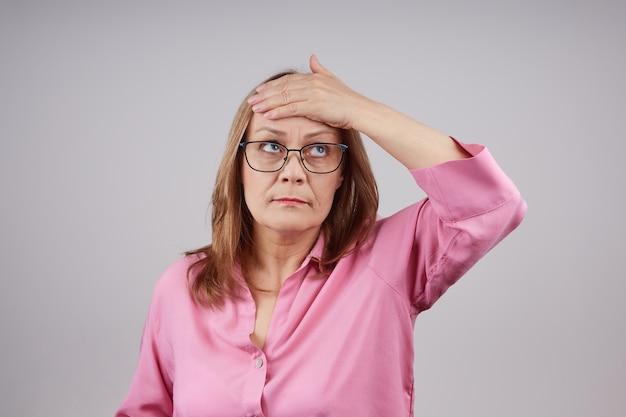 Zakelijke volwassen vrouw met een bril heeft hoofdpijn. studio foto op een grijze achtergrond, met kopie ruimte.