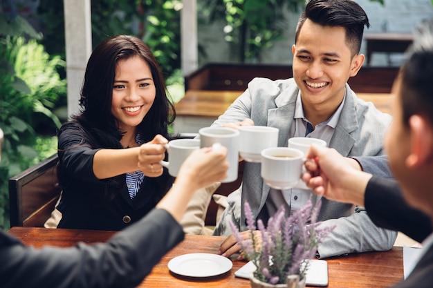 Zakelijke vrienden juichen met koffie in café