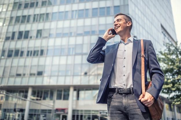 Zakelijke vrijetijdskleding voor man die lacht op een mobiele telefoon voor het kantoorgebouw.