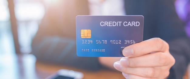 Zakelijke vrouw hand houdt een blauwe creditcard.