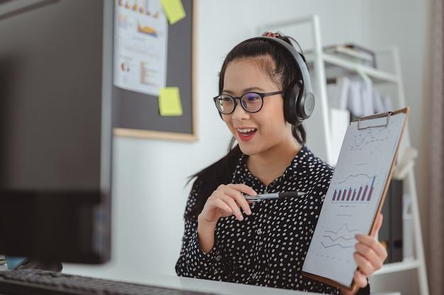 Zakelijke vrouwen die een draadloze koptelefoon dragen die naar het computerscherm kijken, voeren een aangenaam gesprek