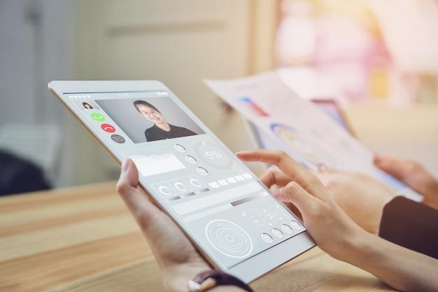 Zakelijke vrouwen gebruiken een tabletscherm met een videogespreksteam.