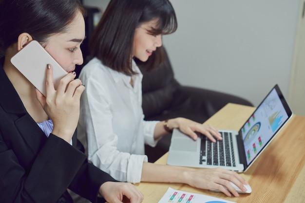 Zakelijke vrouwen gebruiken laptops en smartphones om op kantoor te werken.