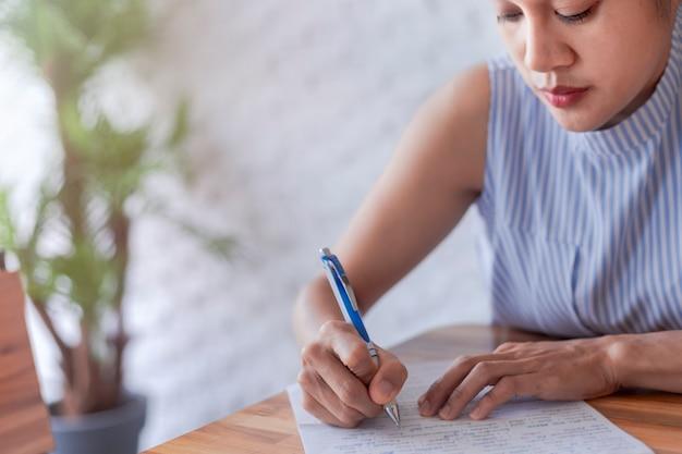Zakelijke vrouwen gebruiken pen om documentpapier te schrijven