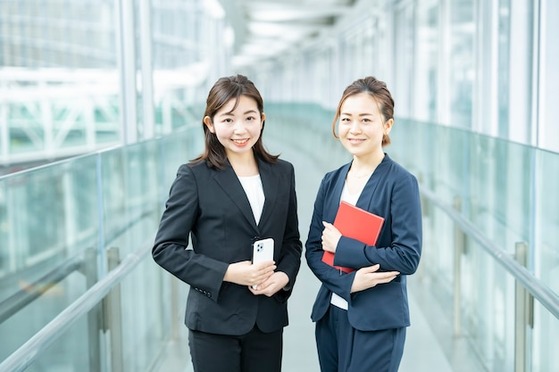 Zakelijke vrouwen kijken naar de camera in de zakenwijk