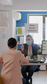 Zakelijke vrouwen met medische gezichtsmaskers praten over managementstatistieken