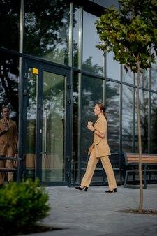 Zakelijke vrouwenstijl. vrouw die met aktentas gaat werken. portret van mooie lachende vrouw in stijlvolle kantoorkleding. hoge resolutie.